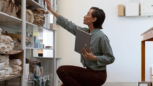 一位女性手持 Surface Pro 7,伸手去够书架
