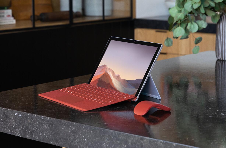 桌子上的 Surface Pro 7 搭配键盘盖和 Arc 鼠标