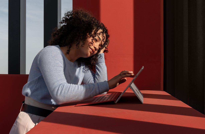 一位女性触控 Surface Pro 7 的屏幕