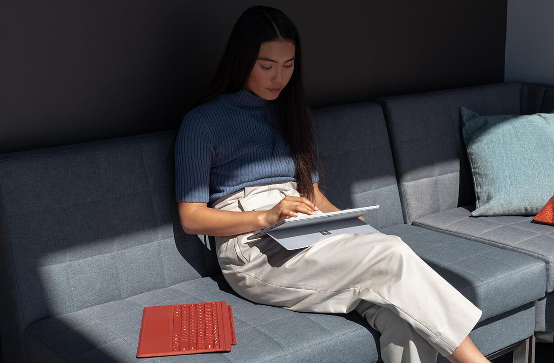 一位女性坐在沙发上工作,膝盖上放着 Surface Pro 7