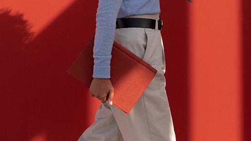 一位女性带着附有波比红键盘盖的 Surface Pro 7 行走