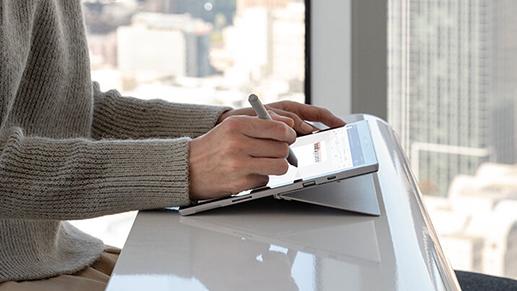 一位女性使用 Surface 触控笔在 Surface Pro 7 上写字