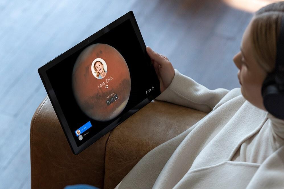 一个人端着 Surface Pro 7 注视着登录屏幕