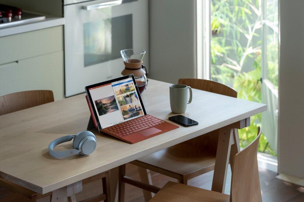 桌上的 Surface Pro 7 旁边放着 Surface Headphones 2 和手机