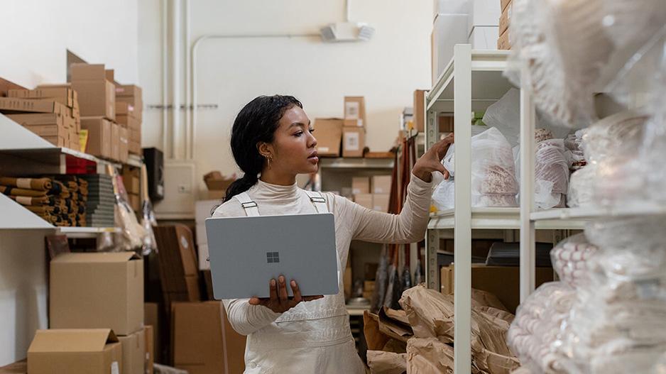 一位女性手持 Surface Laptop 3 去够架子上的物品