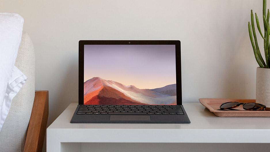 床边的桌子上有一台打开的 Surface Pro 7,附有黑色键盘盖