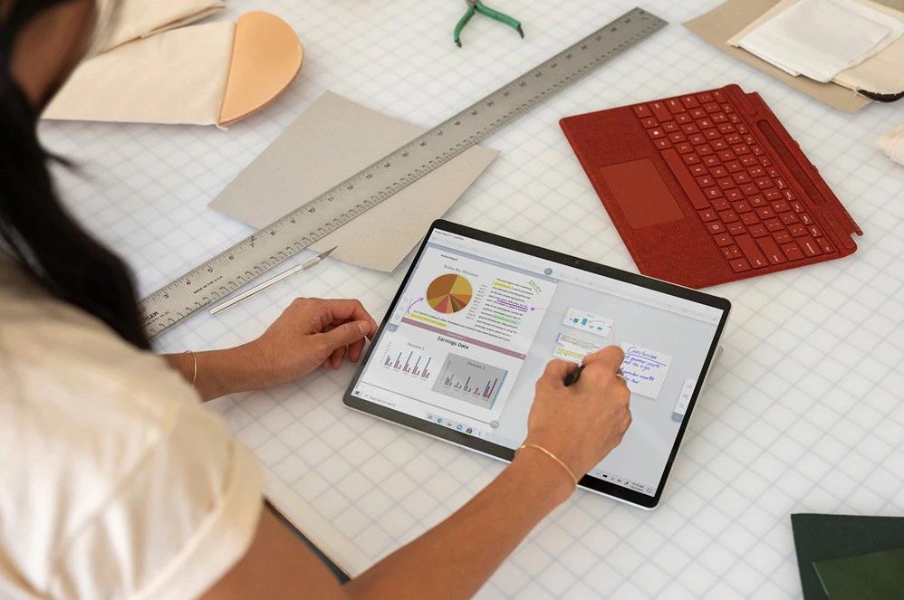 一个人握着超薄触控笔,在平板模式的 Surface Pro X 上使用 Microsoft Word