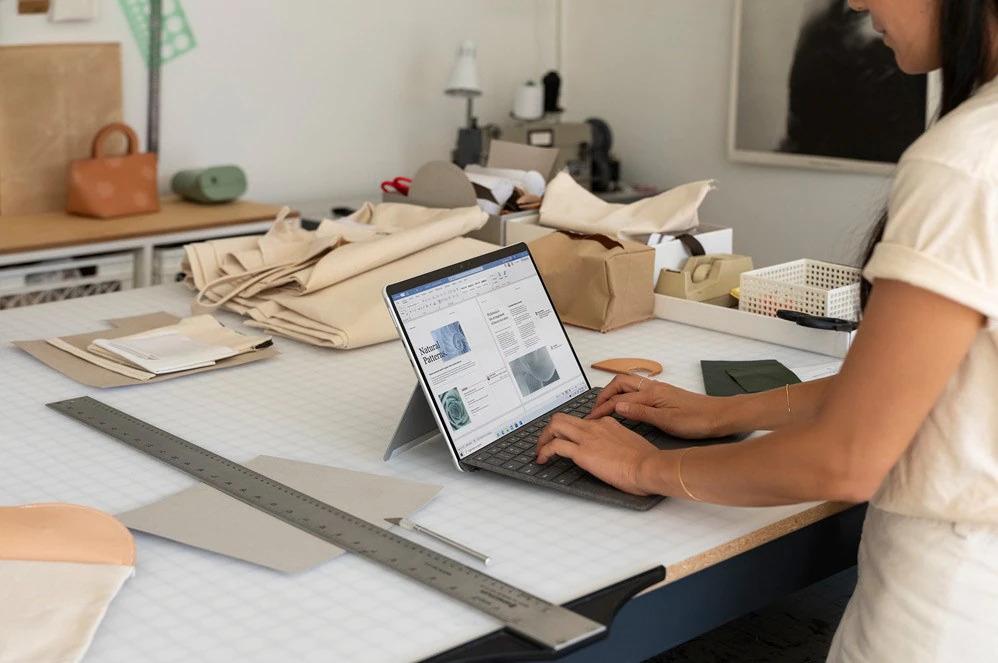 一个人在 Surface Pro X 上使用 Microsoft Word,旁边有一支 Surface 纤细触控笔