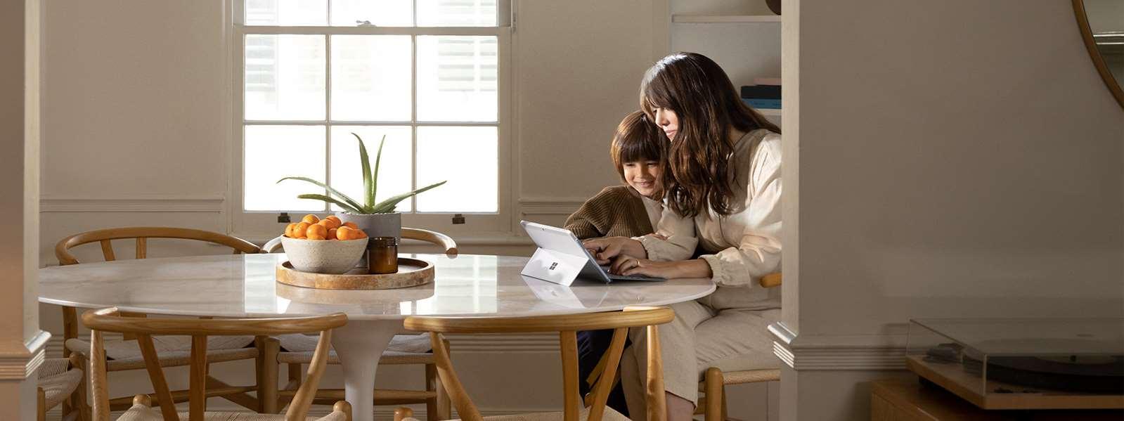 一位女性坐在餐桌旁,她的儿子在玩 Surface Go 2