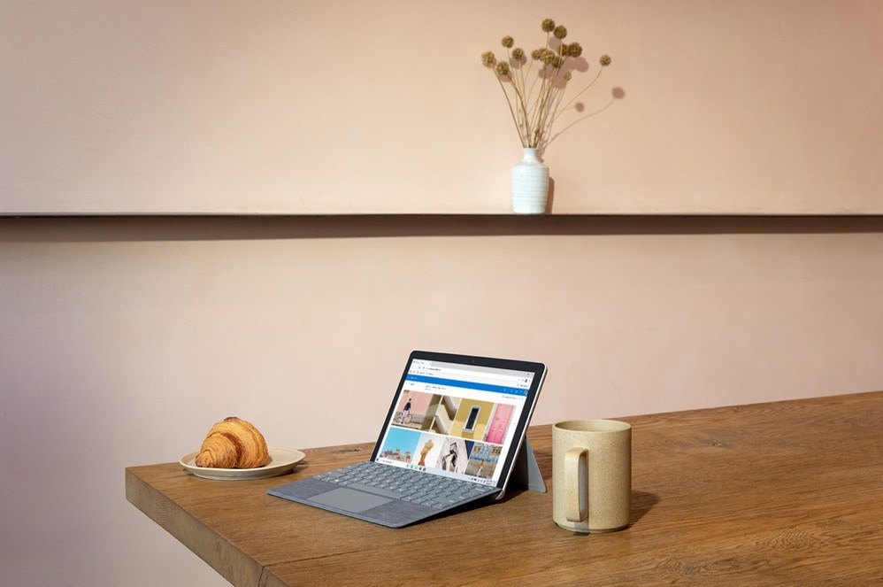 一位女性手持垂直平板电脑模式的 Surface Go 2