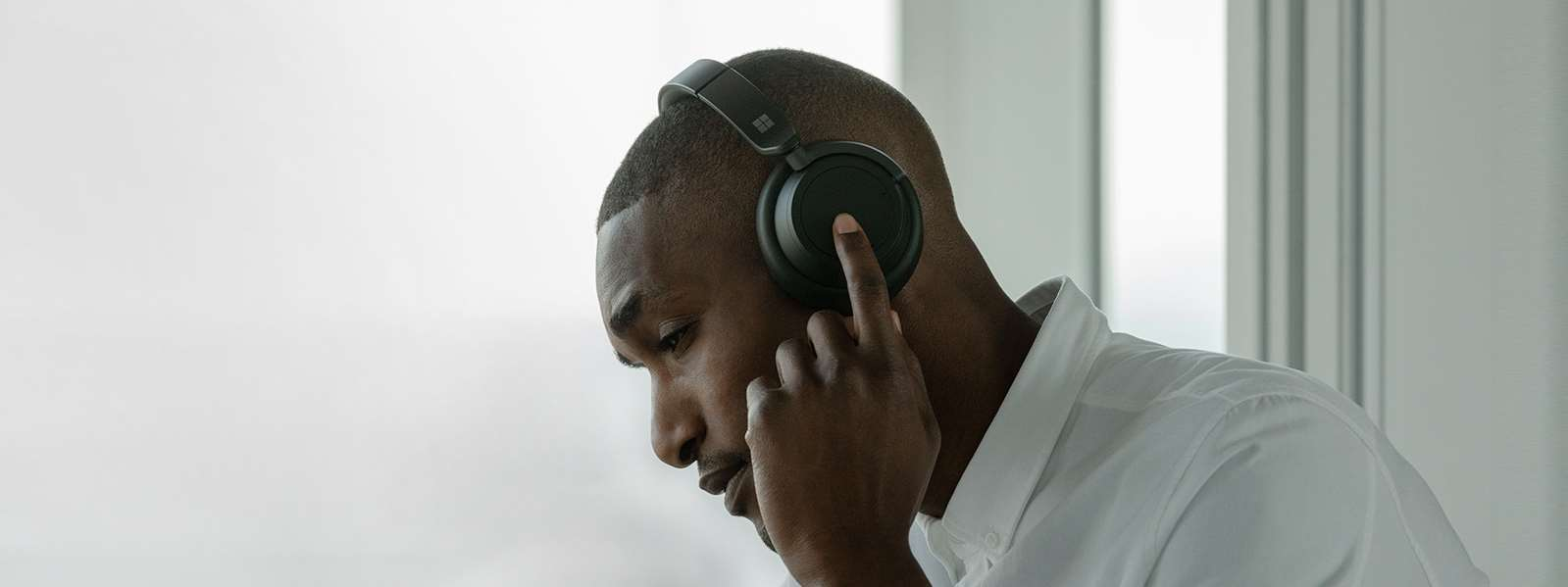 一位佩戴着黑色 Surface Headphone 2 的男士在触控左拨盘