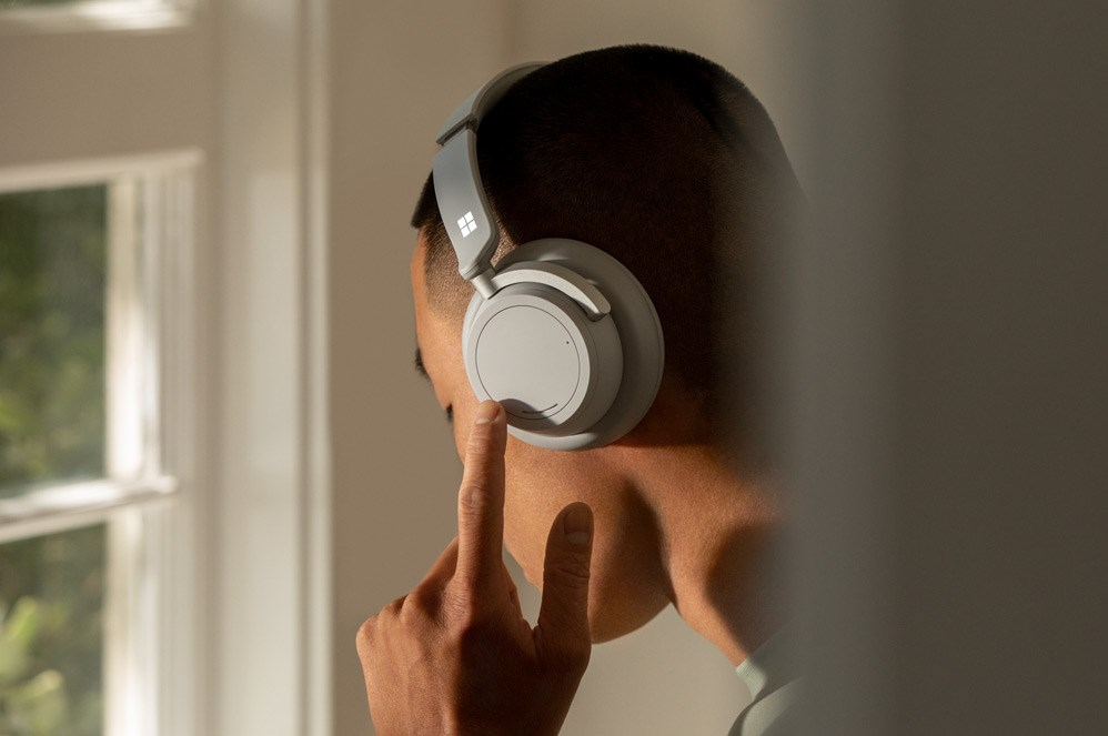 一位男性使用贴耳式左拨盘调整 Surface Headphone 2 的降噪