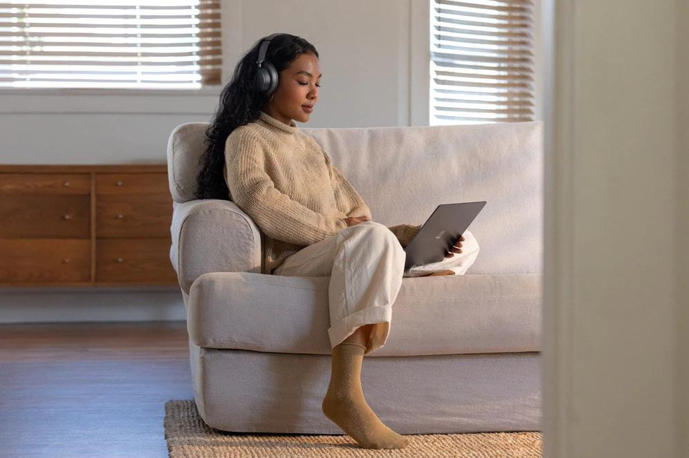 一位女性戴着 Surface Headphone 2 在 Surface 电脑上观看节目