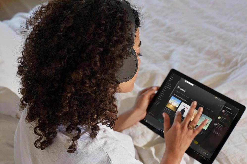 一位女性触控 Surface Headphone 2 右侧以调高音量