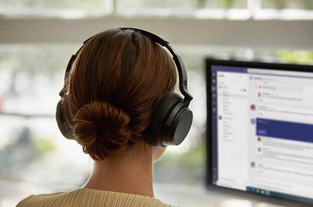 一位女性一边走路一边使用 Surface Headphone 2 对话