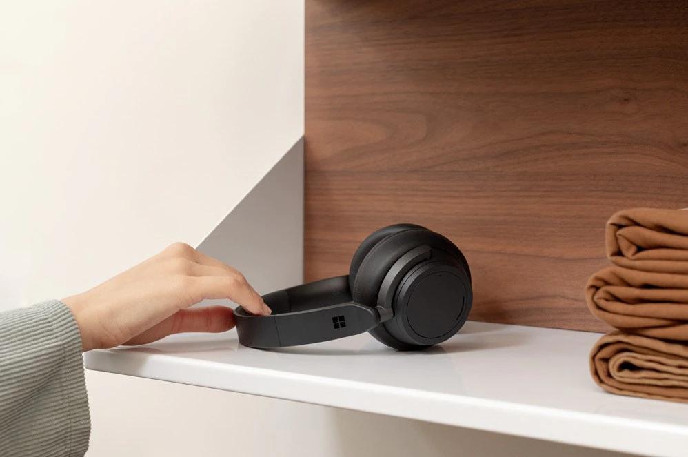 一个人从架子上拿起 Surface Headphone 2