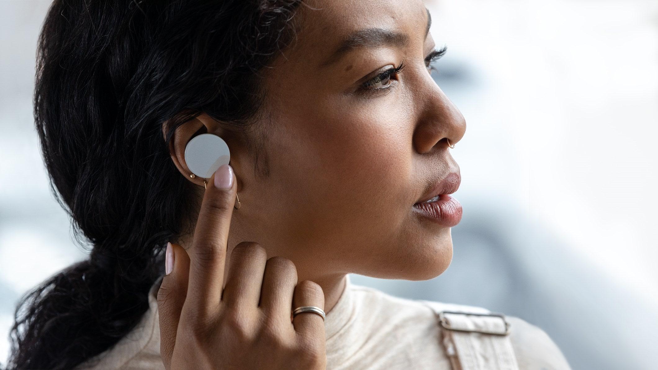 一个女孩戴着 Surface Earbuds
