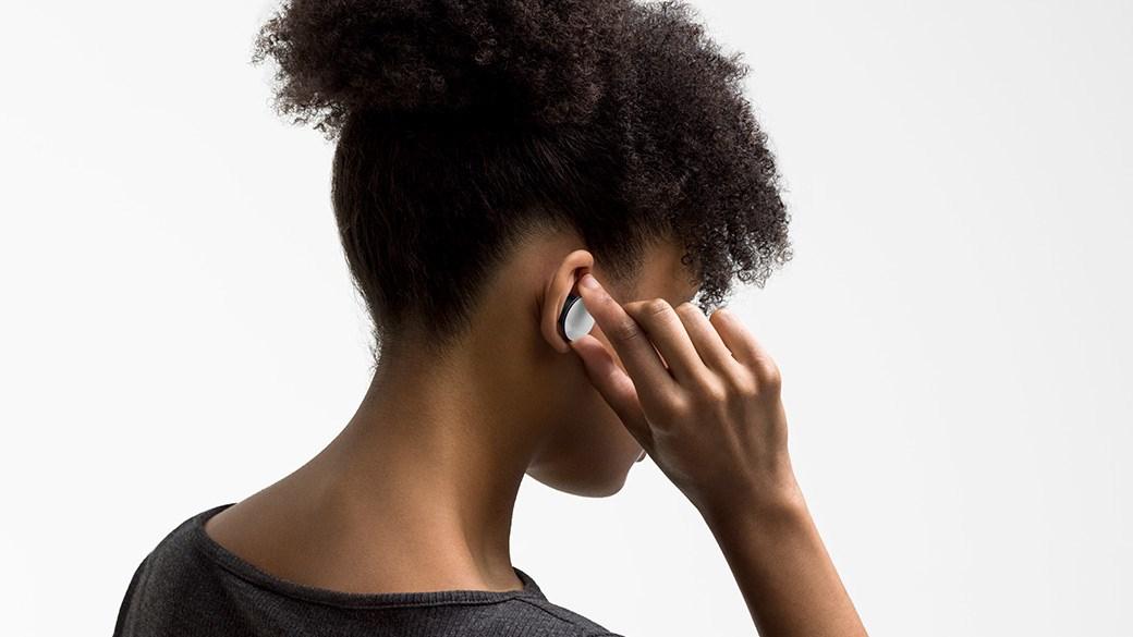 一位戴着 Surface Earbuds,同时滑动以更改音乐曲目。
