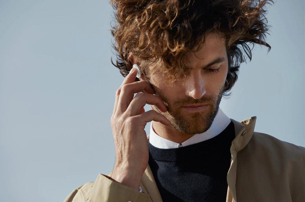 一位男性戴着 Surface Earbuds 讲话同时站在外面做 Surface Pro X