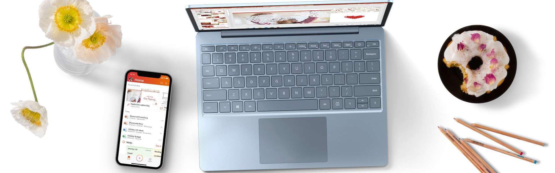 桌上摆放着 Surface Laptop Go、手机、鲜花和一盘甜甜圈
