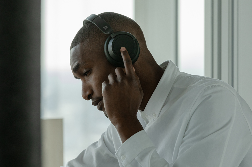 佩戴 Surface Headphones 2+ 的使用者,在一侧耳罩上进行触控操作。