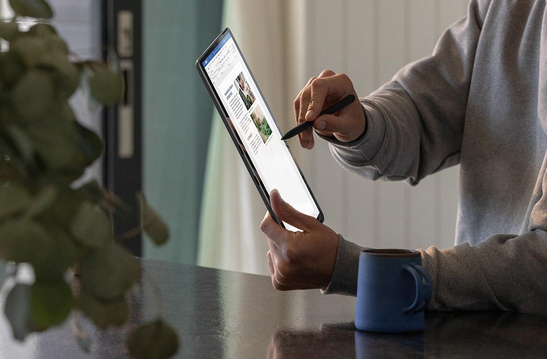 一位男士手持超薄触控笔在平板模式下使用 Surface Pro X 上的 Microsoft Word 工作。