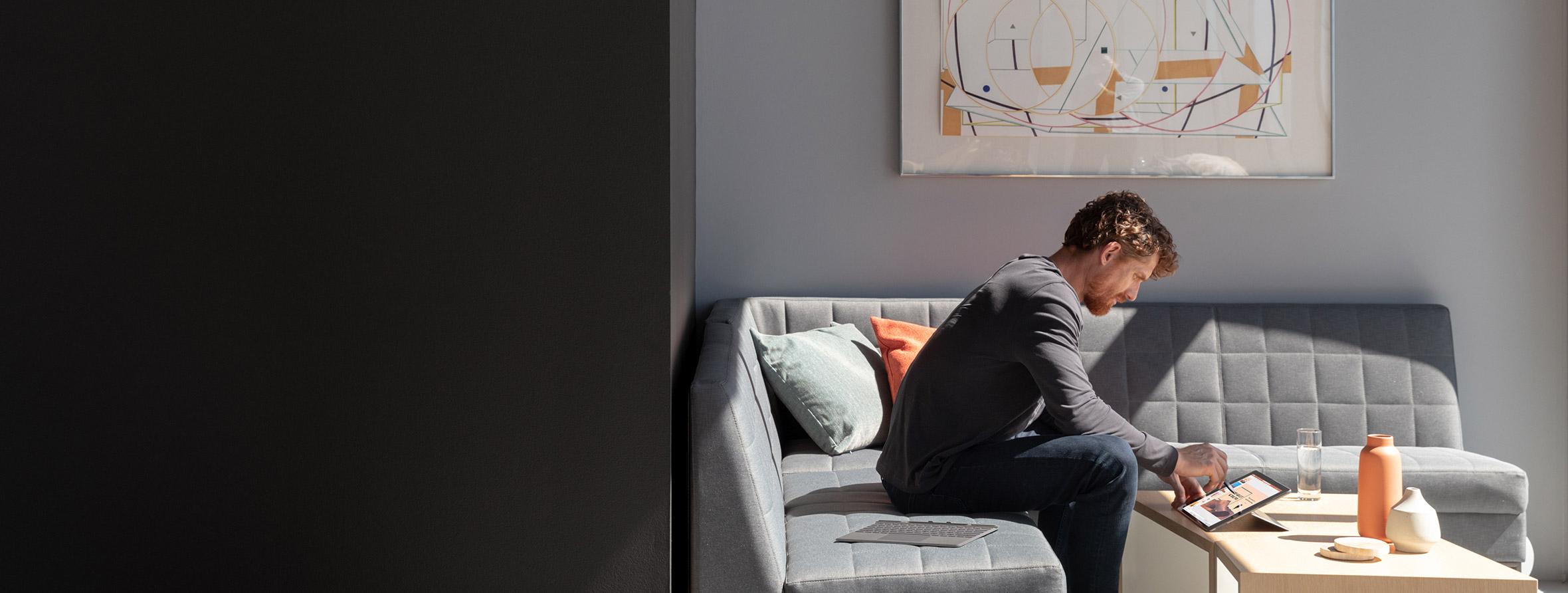 一个人坐在沙发上使用 Surface Pro X 和 Surface 超薄触控笔