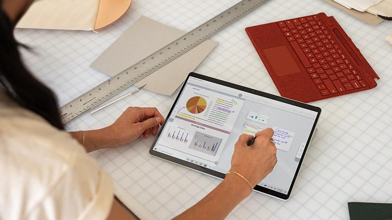 Surface Earbuds 和 Surface Pro X 置于桌面上,Surface 超薄触控笔放在旁边