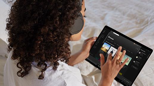 一个人在 Skype 通话中触控 Surface Pro X 的屏幕