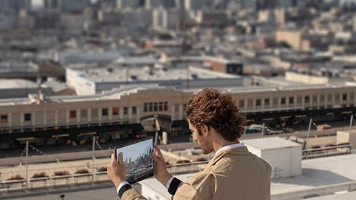 一个人手持 Surface Pro X 拍摄照片