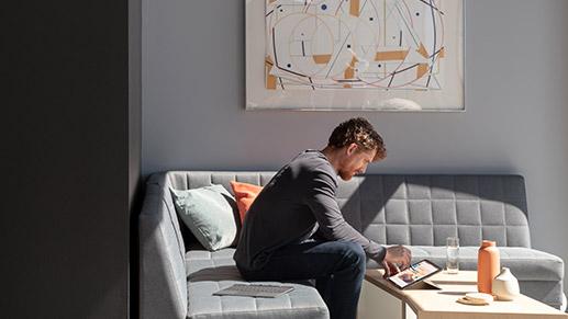 一个人坐在沙发上,使用 Surface 超薄触控笔在 Surface Pro X 上编辑 PowerPoint